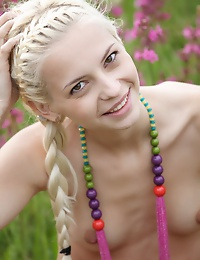 Nice blond teenie with a petite body playfully poses in the nude among the wild flowers.